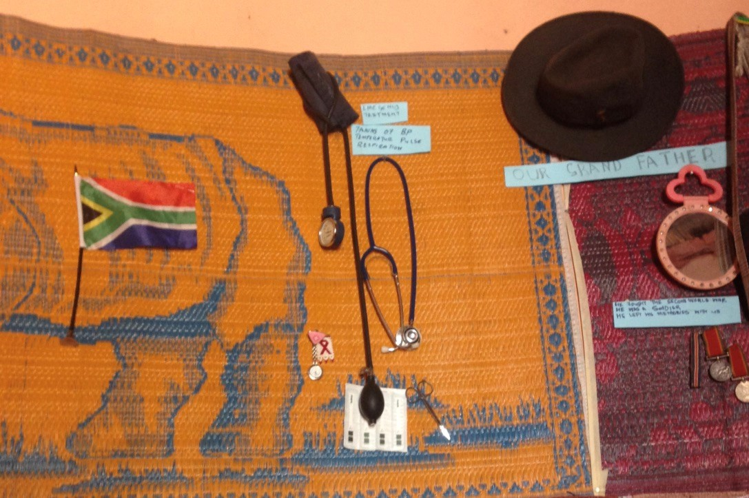 Caption: Indumba/THP consultation space of a nurse – Limpopo. Stethoscope and blood pressure machine on the wall next to her grandfather's hat, mirror and medals for fighting in the second world war. She had labelled these, alongside many other items, to teach us about her practice, which combines both biomedical and traditional healthcare.